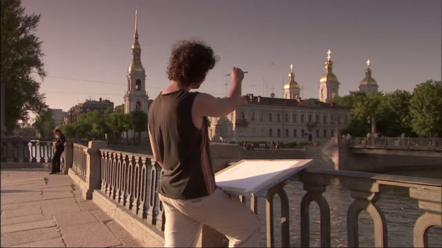 an artist stands on a bridge and sketches a distant building. - st. petersburg russia stock videos & royalty-free footage