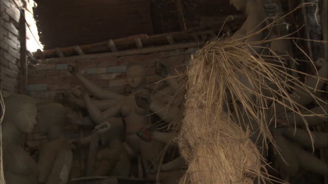 an artist ties the base of a straw effigy available in hd. - effigy stock videos & royalty-free footage