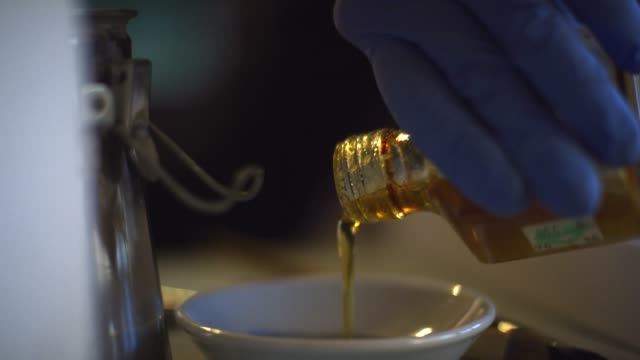 an artist wearing protective gloves pours linseed oil (paint thinner / brush cleaner) into a small bowl in preparation for painting - oil paint stock videos and b-roll footage