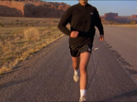 vidéos et rushes de an asain woman running on road in southwest outdoors - seulement des jeunes femmes