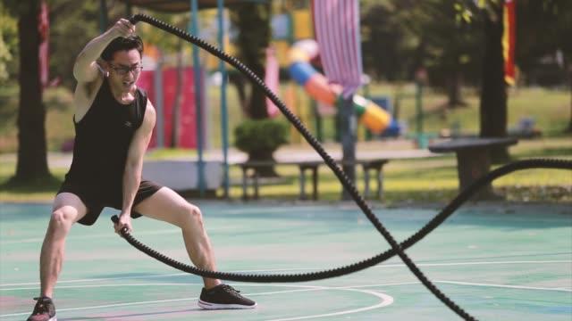 vidéos et rushes de une gymnastique d'homme mûr chinoise d'asie dans le parc public. il s'entraîne à l'aide de la corde de combat. - effort