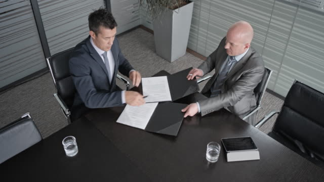 CS An Asian and a Caucasian businessman signing a contract in conference room and shaking hands