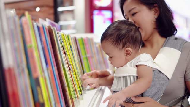 an asian baby boy with his mother holding in the bookstore. - arts culture and entertainment stock videos & royalty-free footage