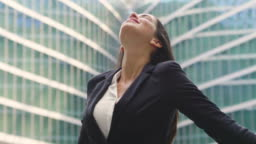An asian business woman, dressed in a suit, raises her arms to the sky and breathes as a sign of freedom and success in her work.