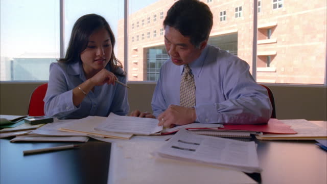 an asian businesswoman and businessman work at a desk. - ビジネスフォーマル点の映像素材/bロール
