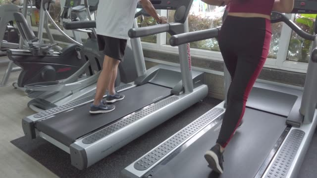 an asian chinese active senior man exercising with his granddaughter in gym with treadmill - treadmill stock videos & royalty-free footage