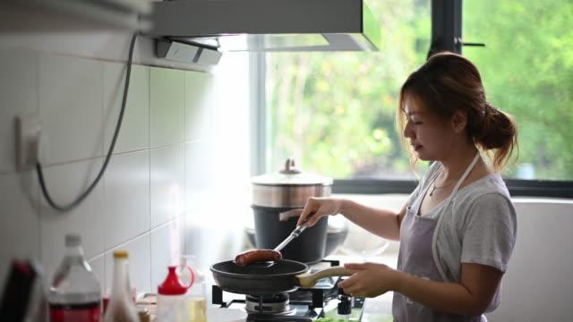 朝食の準備をしている台所で卵を揚げるアジアの中国の美しい女性 - 家事点の映像素材/bロール