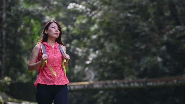 アジアの中国の美しい女性ジャングルトレッキング - 小道点の映像素材/bロール