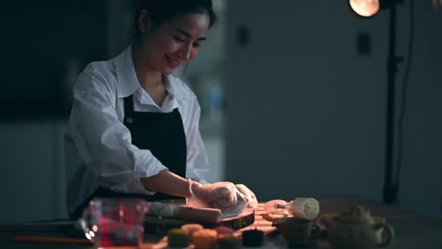 vidéos et rushes de une belle femme chinoise asiatique faisant le gâteau traditionnel chinois de peau de neige de mi-automne à sa cuisine - malaysian culture