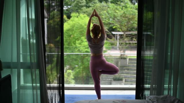 vídeos de stock, filmes e b-roll de uma mulher asiática chinesa bonita praticando yoga em sua casa de manhã em sua varanda - pose de arvore