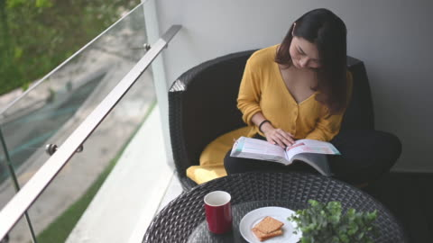 vídeos y material grabado en eventos de stock de una hermosa mujer asiática china leyendo libro en su balcón durante el mediodía relajarse y disfrutar de su tiempo desintoxicante digital me con café y galleta para la merienda - pasatiempos