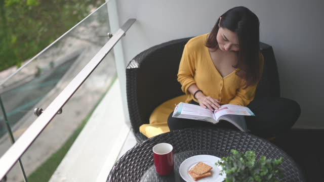 an asian chinese beautiful woman reading book in her balcony during noon relaxing and enjoying her digital detox me-time with coffee and biscuit for snack - south east asian ethnicity stock videos & royalty-free footage