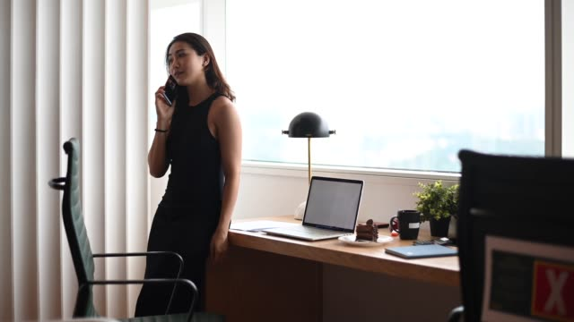 an asian chinese beautiful woman white collar worker working in the office listening to her phone - authority stock videos & royalty-free footage