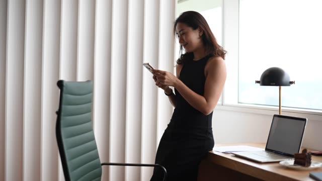 彼女の携帯電話を聞いてオフィスで働くアジアの中国の美しい女性ホワイトカラー労働者 - white collar worker点の映像素材/bロール
