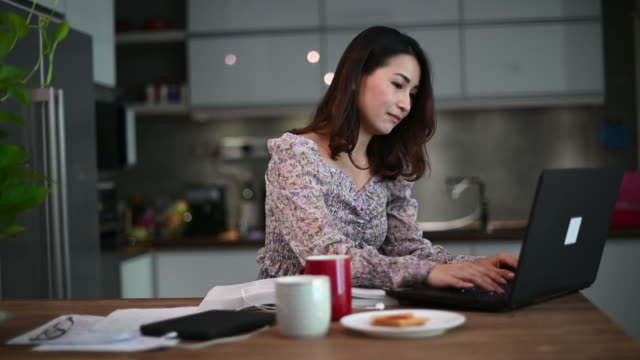 an asian chinese beautiful woman working from home as customer service answering to her customer online using laptop   in the kitchen typing - chinese ethnicity stock videos & royalty-free footage