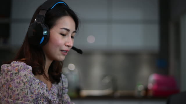 an asian chinese beautiful woman working from home as customer service answering to her customer online using laptop and headphone in the kitchen typing - headset stock videos & royalty-free footage