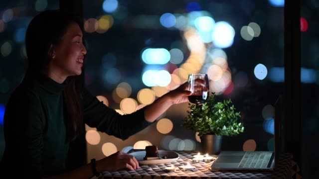 an asian chinese beautiful young lady having dessert in her apartment during magic hour, dusk and talking to her boyfriend thru internet using her laptop - refreshment stock videos & royalty-free footage