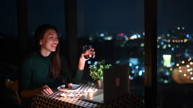 an asian chinese beautiful young lady having dessert in her apartment during magic hour, dusk and talking to her boyfriend thru internet using her laptop - virtual event stock videos & royalty-free footage