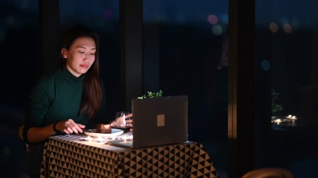 an asian chinese beautiful young lady having dessert in her apartment during magic hour, dusk and talking to her boyfriend thru internet using her laptop - dating stock videos & royalty-free footage