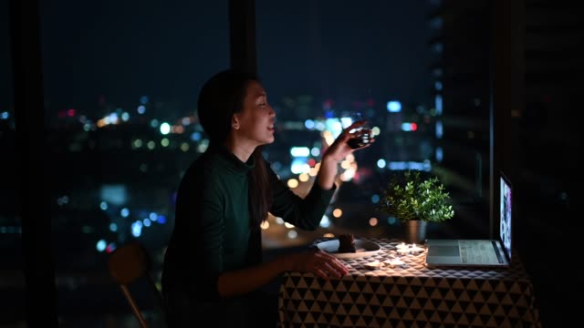 an asian chinese beautiful young lady having dessert in her apartment during magic hour, dusk and talking to her boyfriend thru internet using her laptop - dessert stock videos & royalty-free footage