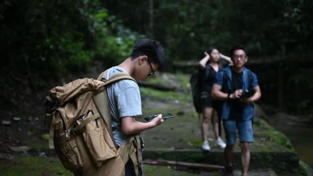 自然公園で両親と一緒にハイキングをしながらスマートフォンを見ているアジアの中国人の少年 - rainforest点の映像素材/bロール