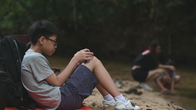stockvideo's en b-roll-footage met een aziatische chinese jongen die alleen bij de riverside zit die mobiele spelen met zijn slimme telefoon speelt terwijl zijn zuster en moeder die in de rivier in het bos tijdens weekend spelen - chinese etniciteit