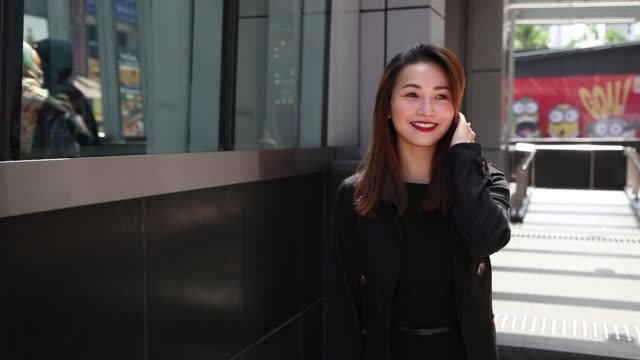 an asian chinese business lady walking toward the camera in the street