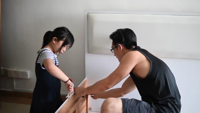 vídeos de stock, filmes e b-roll de uma família asiática chinesa mudança casa filha ajudando seu pai montar quadro de cama - mobília