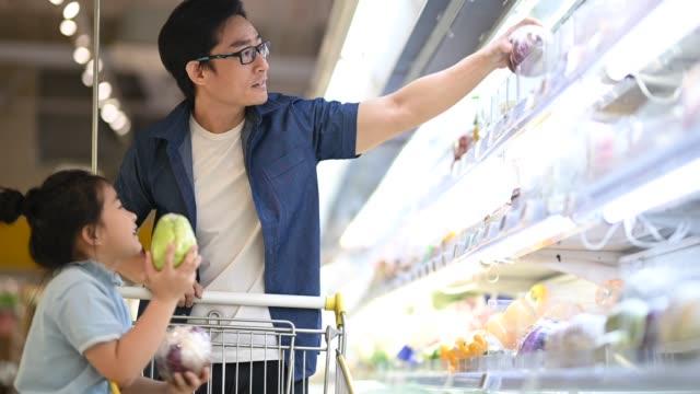 アジアの中国人の父と娘が食料品店の冷蔵庫野菜部門で買い物をする野菜を選んで買う - buying点の映像素材/bロール
