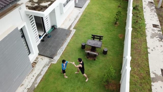 vídeos y material grabado en eventos de stock de un atleta padre chino asiático entrenando a su hijo de 12 años en el patio de la casa en el arte marcial de la noche - son