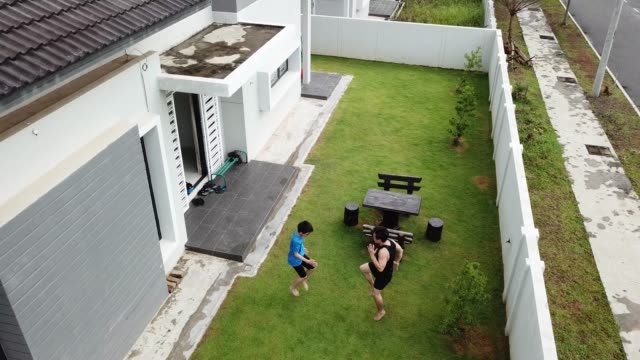an asian chinese father athlete training his 12 years son in front yard of house in the evening - competition stock videos & royalty-free footage
