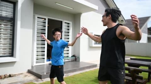 アジアの中国の父親アスリートは、夕方のジャンプで家の前庭で彼の12歳の息子を訓練 - active lifestyle点の映像素材/bロール