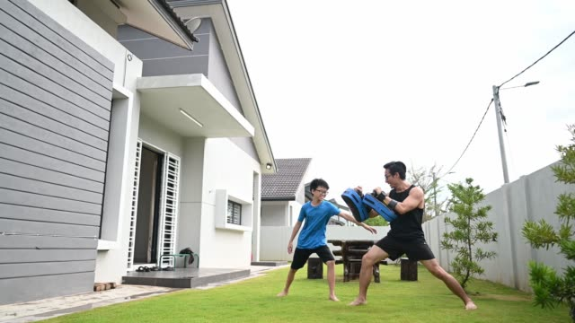 an asian chinese father athlete training his 12 years son in front yard of house in the evening kickboxing - kickboxing stock videos & royalty-free footage