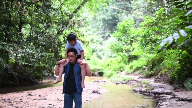 vídeos y material grabado en eventos de stock de un padre chino asiático que lleva a su hija en el hombro en la selva disfrutando de uniendo tiempo juntos en el río durante el fin de semana de ocio - área silvestre