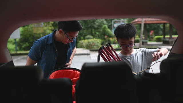an asian chinese father getting ready for hiking packing from his car boot with his son - ethnicity stock videos & royalty-free footage
