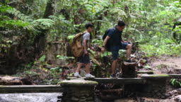 an asian chinese father hiking and exploring forest with his son looking at mobile app on map for direction navigation