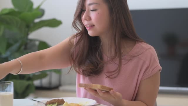 an asian chinese female applying butter using butter knife on the bread during breakfast in dining room - breakfast room stock videos & royalty-free footage