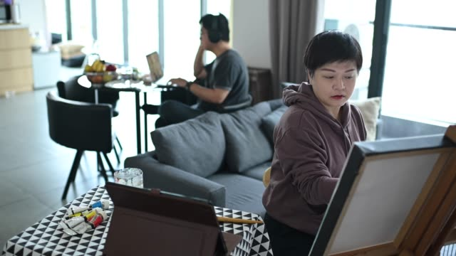 an asian chinese female artist drawing at home with her color palette, paint brush and art paper on easel in living room listening to music using her headphone while her husband working in dining room - husband stock videos & royalty-free footage
