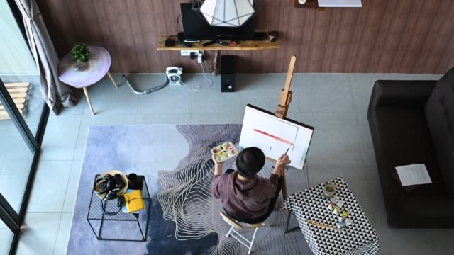an asian chinese female artist drawing at home with her color palette, paint brush and art paper on easel in living room from directly above - artist stock videos & royalty-free footage