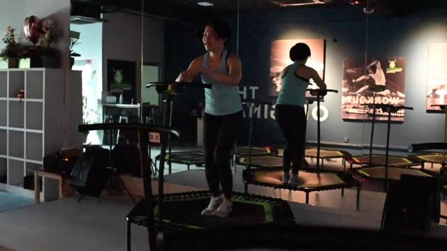 vidéos et rushes de une athlète féminine chinoise asiatique sautant sur un trampoline dans son atelier - entraînement cardiovasculaire