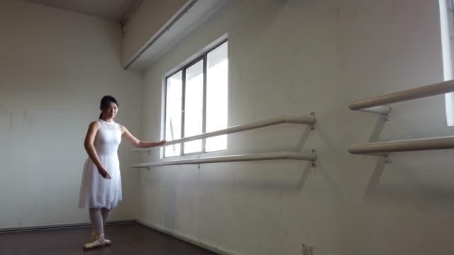 アジアの中国の女性バレエダンサーがダンススタジオで練習し、床に倒れた - バレリーナ点の映像素材/bロール