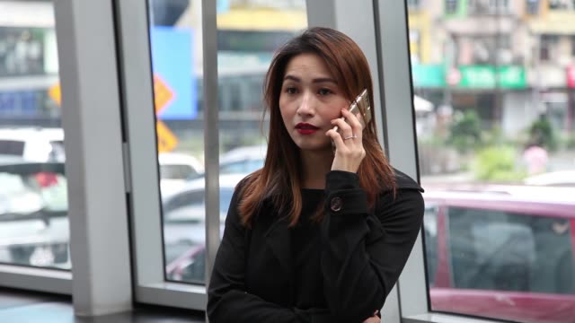 an asian chinese female business lady talking over mobile phone