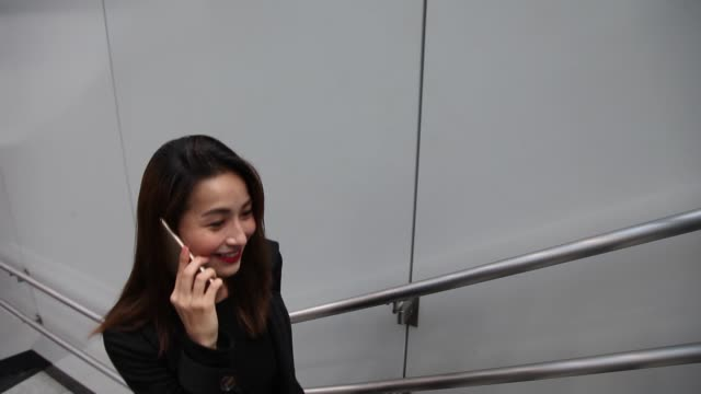 an asian chinese female business lady talking over mobile phone while walking up from staircase