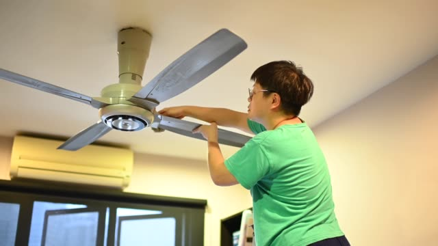 an asian chinese female cleaning ceiling fan at home - stereotypical stock videos & royalty-free footage