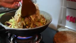 an asian chinese female cooking at home chinese food fried noodle on cooking pan on stove