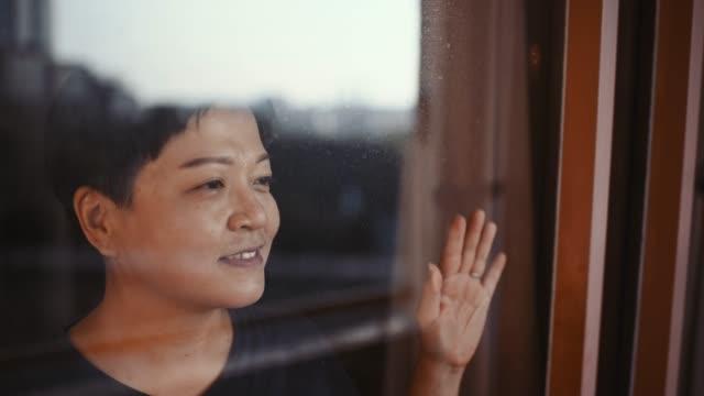 vidéos et rushes de une femelle chinoise asiatique regardant par sa fenêtre de balcon avec le sourire de réflexion - au loin