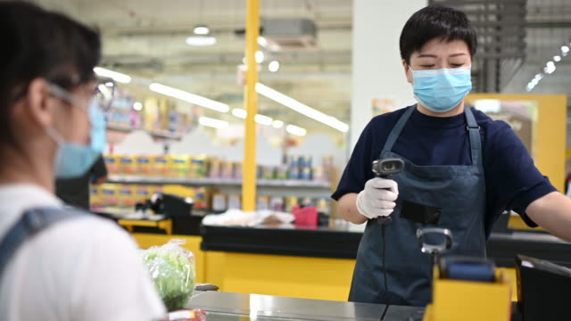 an asian chinese female supermarket retailer shop assistant cashier scanning vegetable for the pricing during checkout at counter - shop assistant stock videos & royalty-free footage