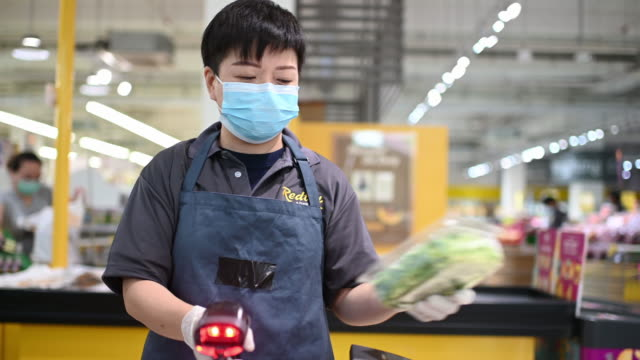 an asian chinese female supermarket retailer shop assistant cashier scanning vegetable for the pricing during checkout at counter - greengrocer stock videos & royalty-free footage