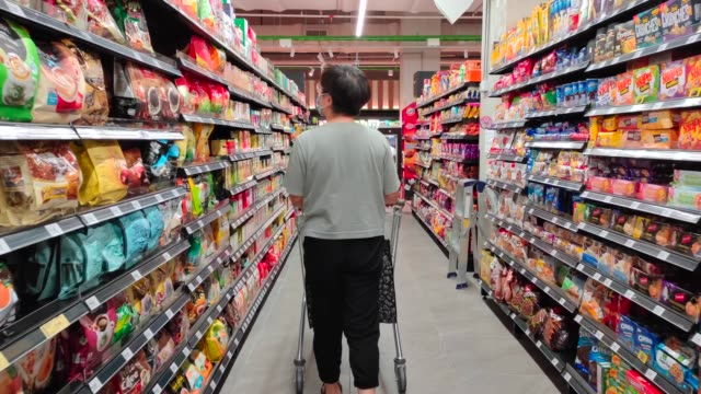 an asian chinese female wearing a mask going out shopping in supermarket buying grocery - rear view stock videos & royalty-free footage