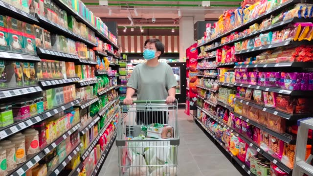an asian chinese female wearing a mask going out shopping in supermarket buying grocery - cultura malesiana video stock e b–roll